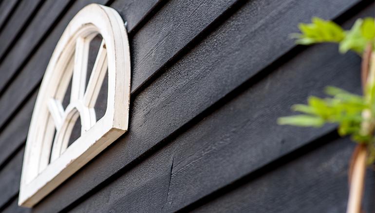 Schuurwoning met een houten gevelbekleding en wit raam